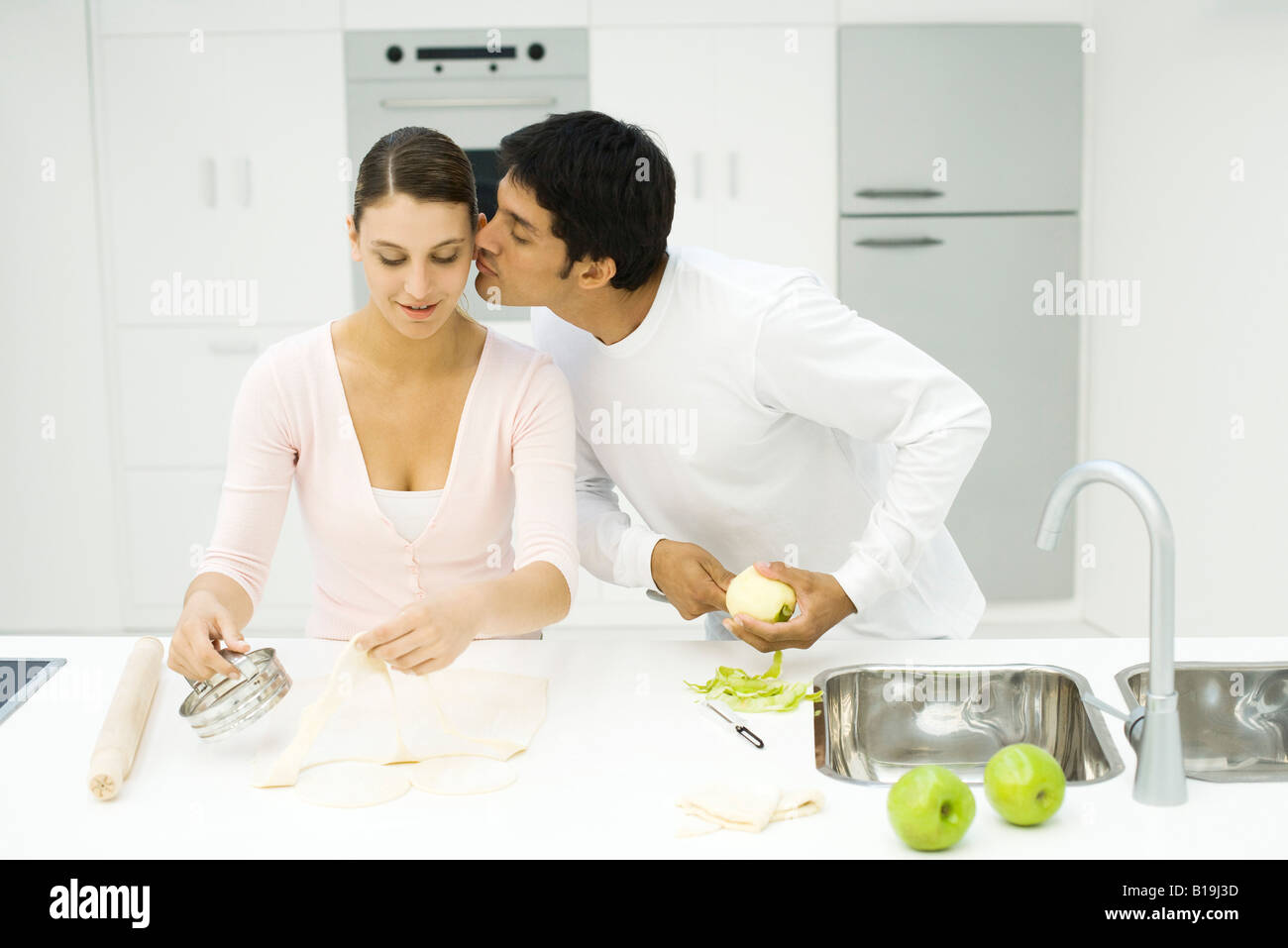 Couple cooking together, man kissing woman's cheek - Stock Image
