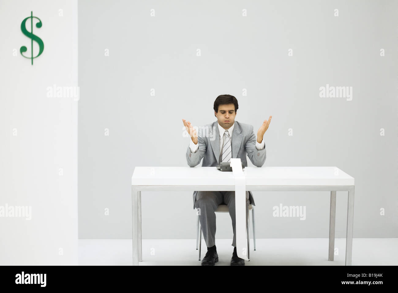 Man sitting at desk with adding machine, puffed cheeks, hands raised - Stock Image