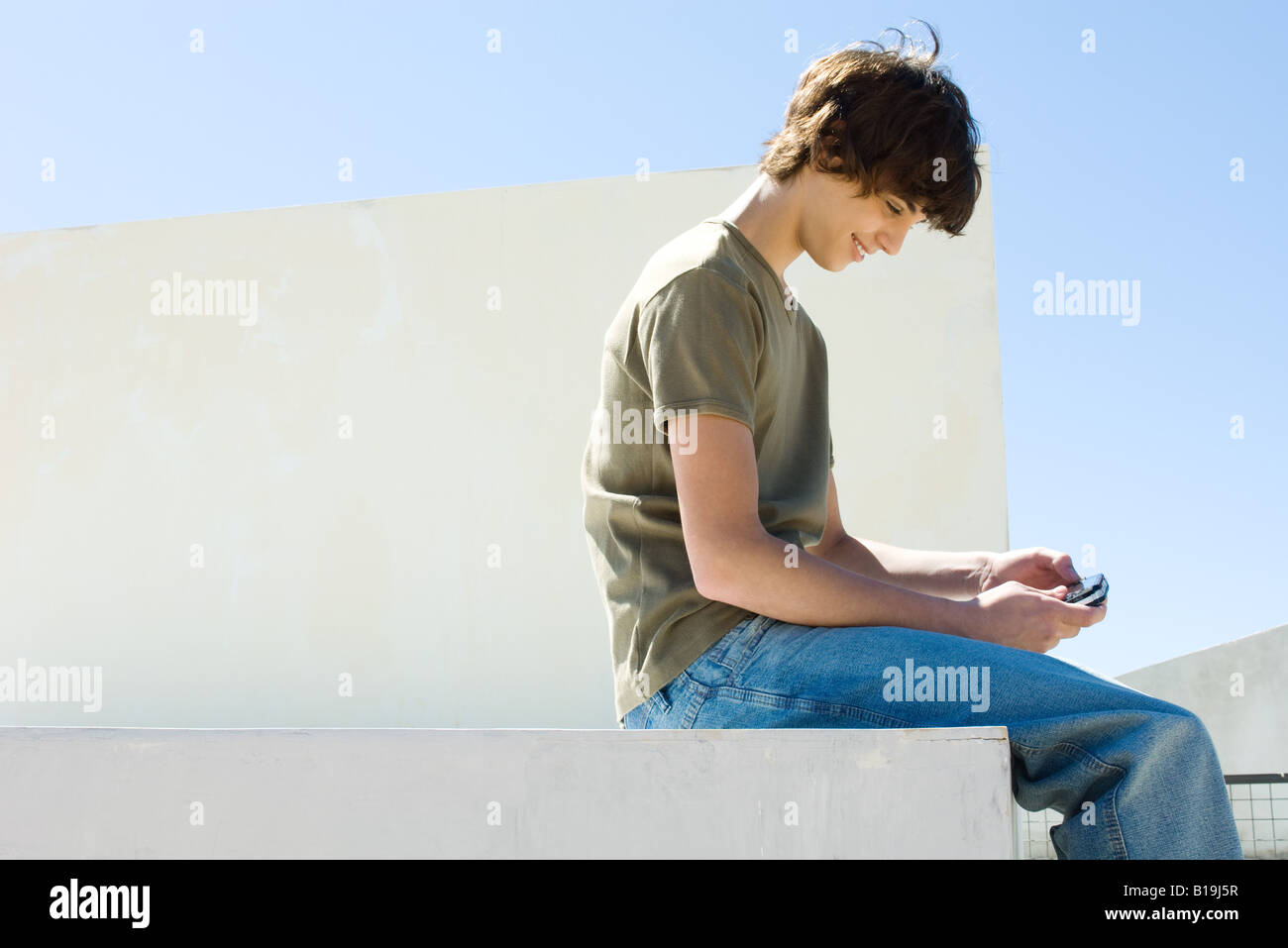 Teen boy playing handheld video game outdoors Stock Photo