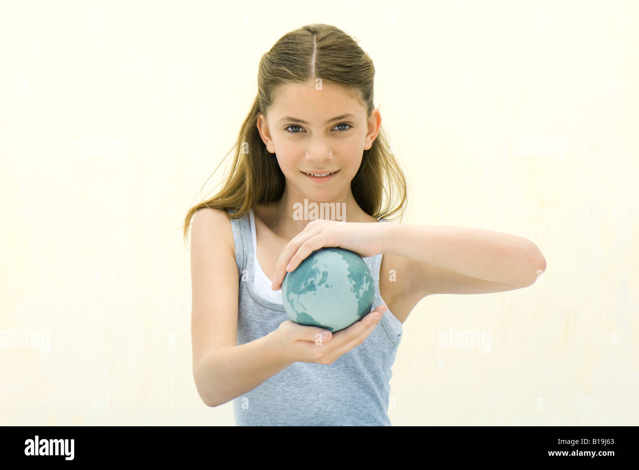 Preteen girl holding small globe in hands, smiling at camera - Stock Image