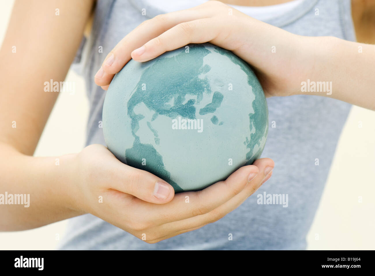 Child holding globe in hands, close-up - Stock Image