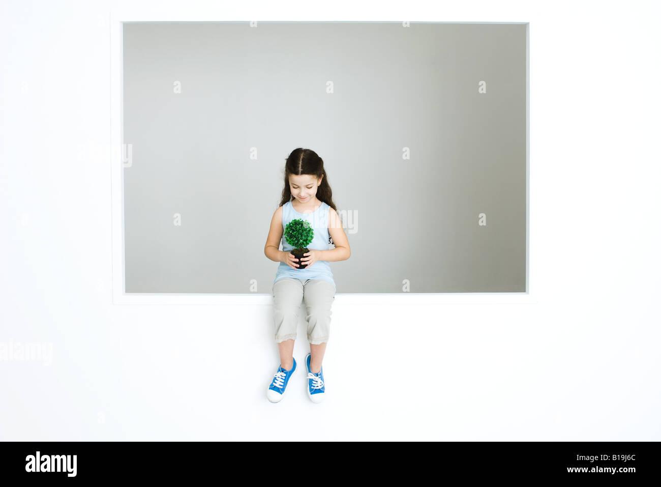 Little girl holding plant, full length Stock Photo