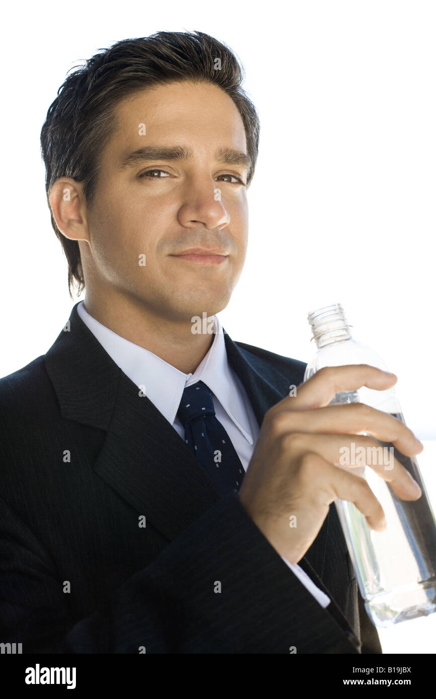 Businessman holding water bottle, looking at the camera, portrait - Stock Image
