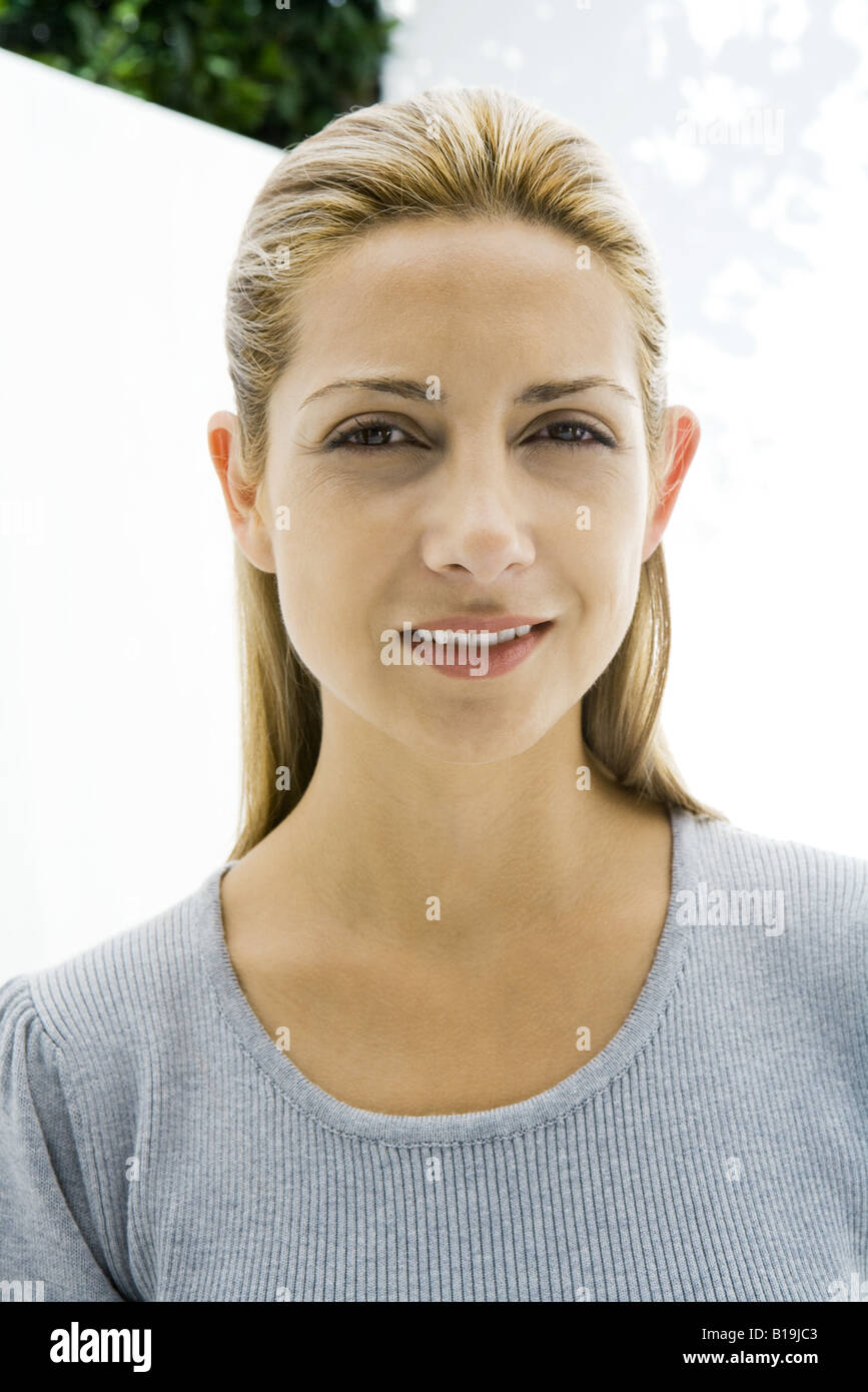 Blonde woman smiling at camera, portrait - Stock Image