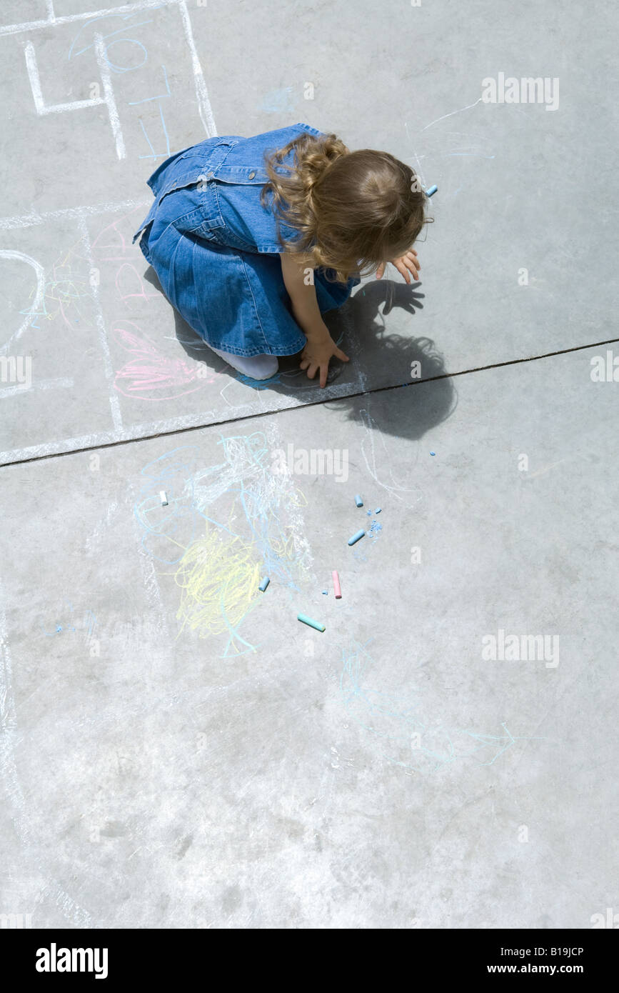 Girl playing with chalk, hunched over, high angle view - Stock Image