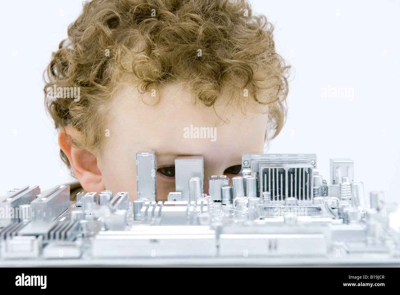 Curly haired boy hiding behind and looking through circuit board - Stock Image