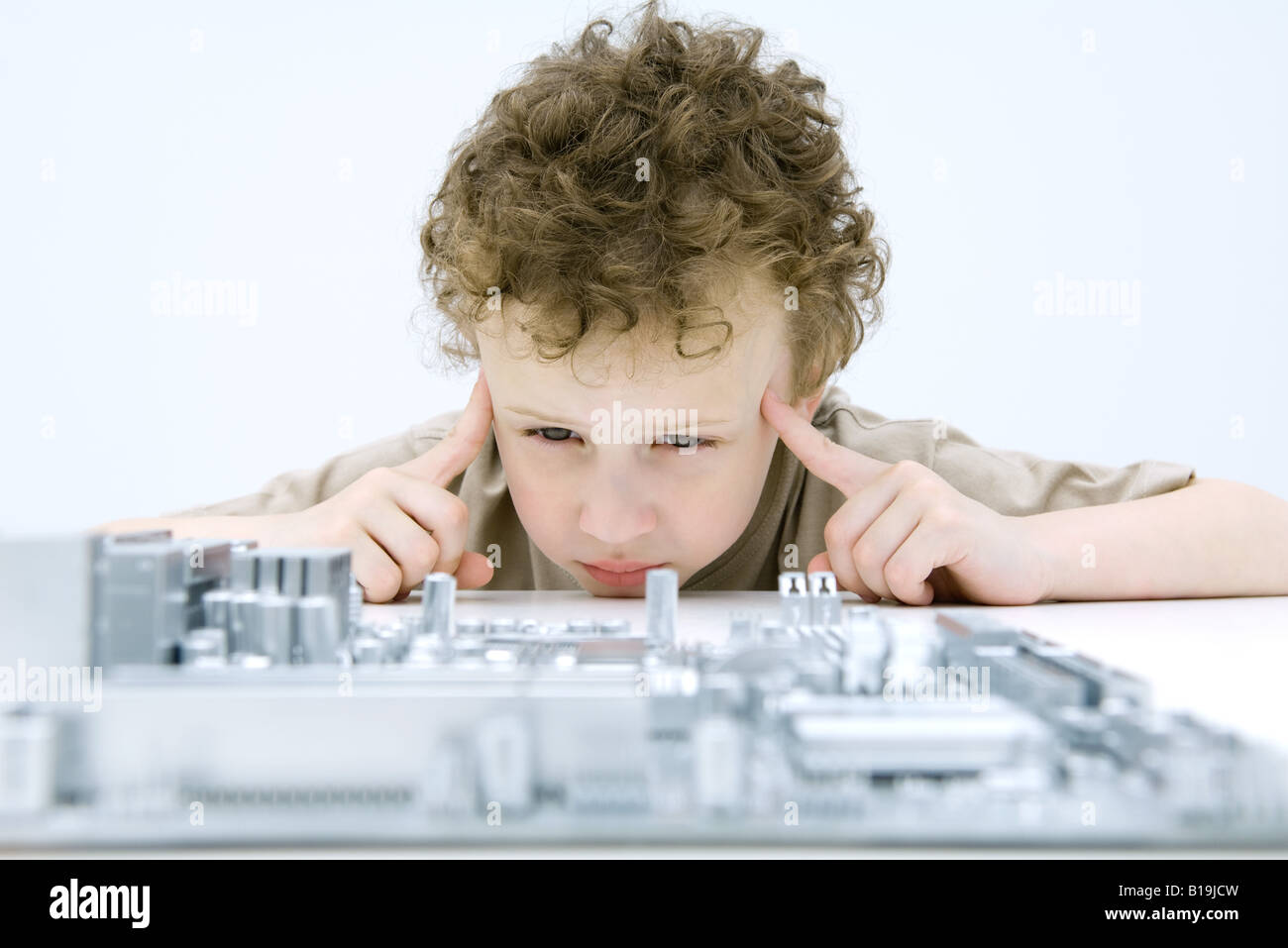 Boy looking at circuit board, holding fingers to his temples - Stock Image