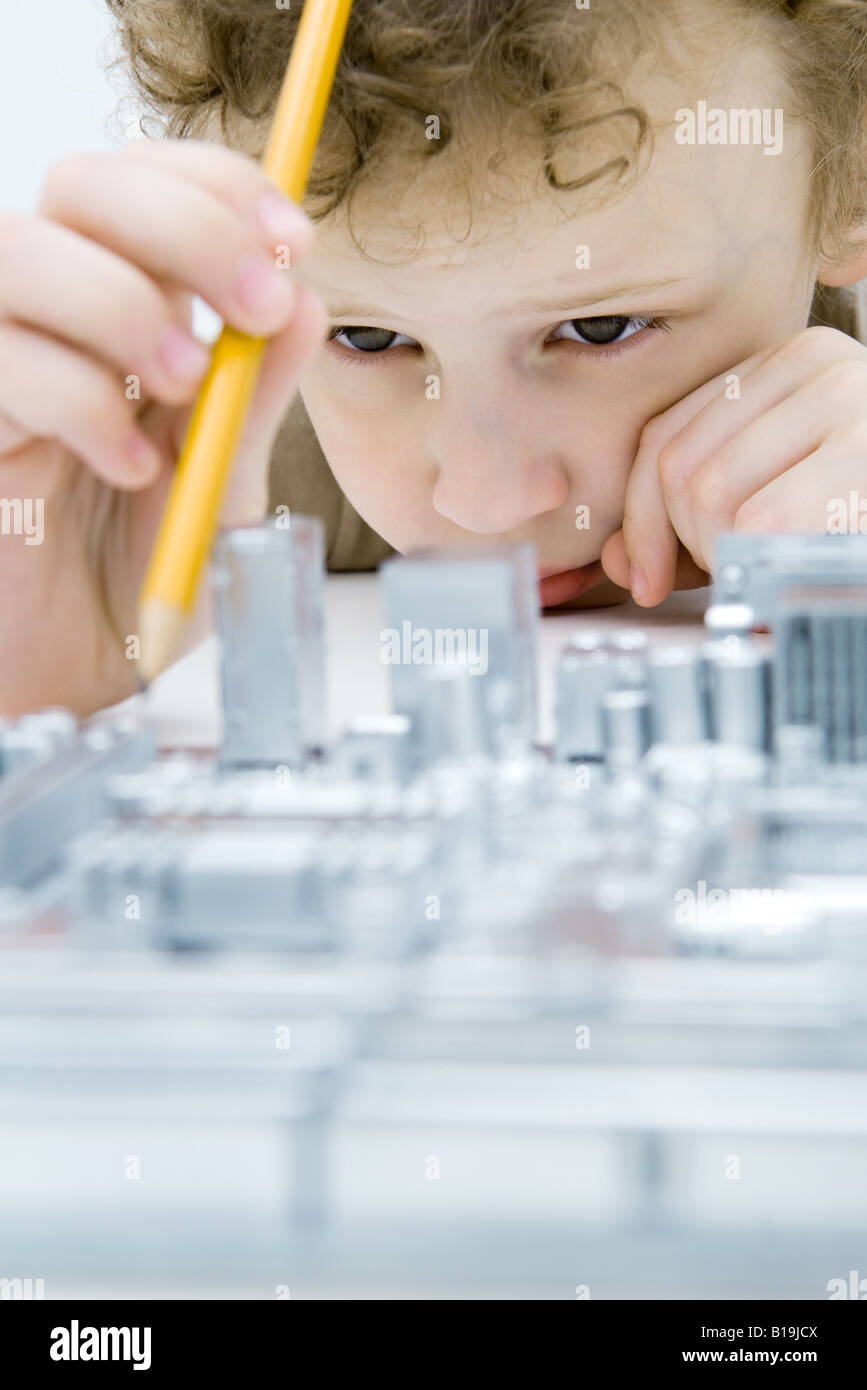 Little boy looking at circuit board, holding pencil, close-up - Stock Image