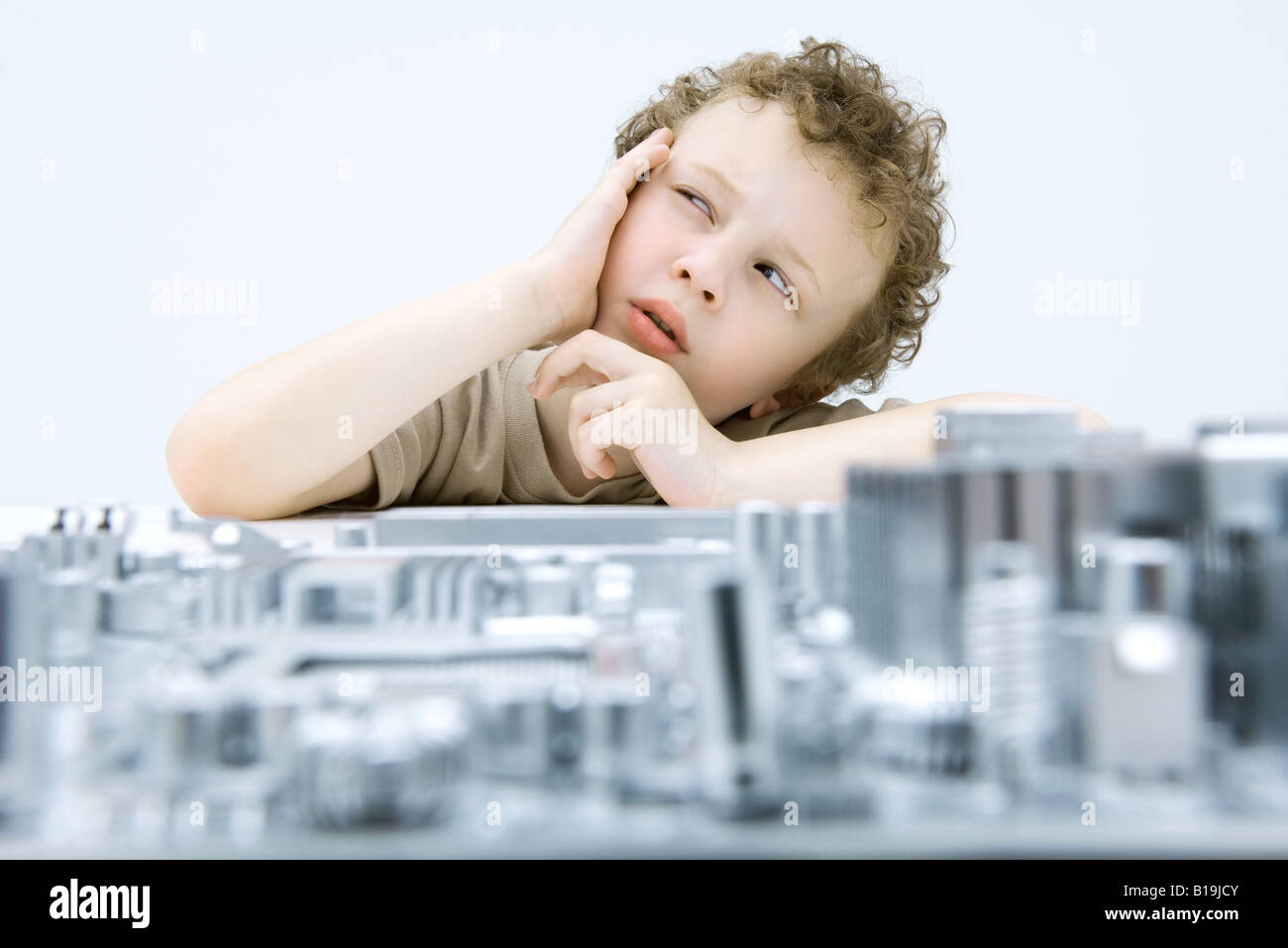 Little boy next to circuit board, holding head, looking up - Stock Image