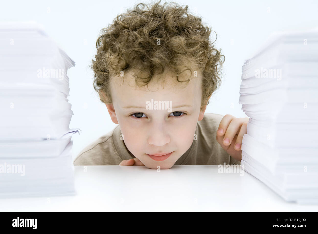Curly haired boy peering between stacks of paper, smiling at camera - Stock Image