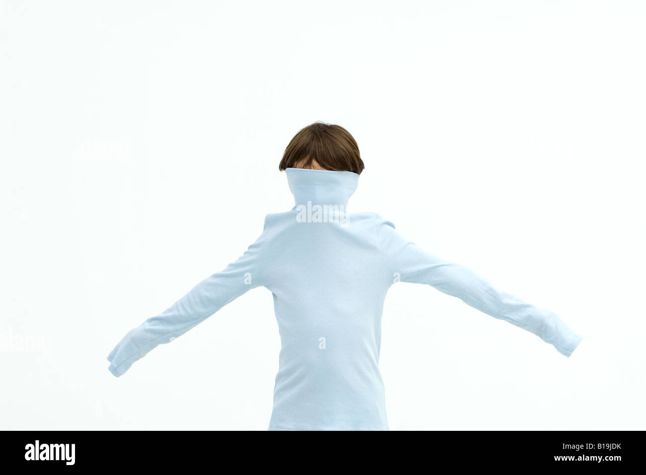 Boy wearing turtleneck pulled over his face, arms outstretched - Stock Image