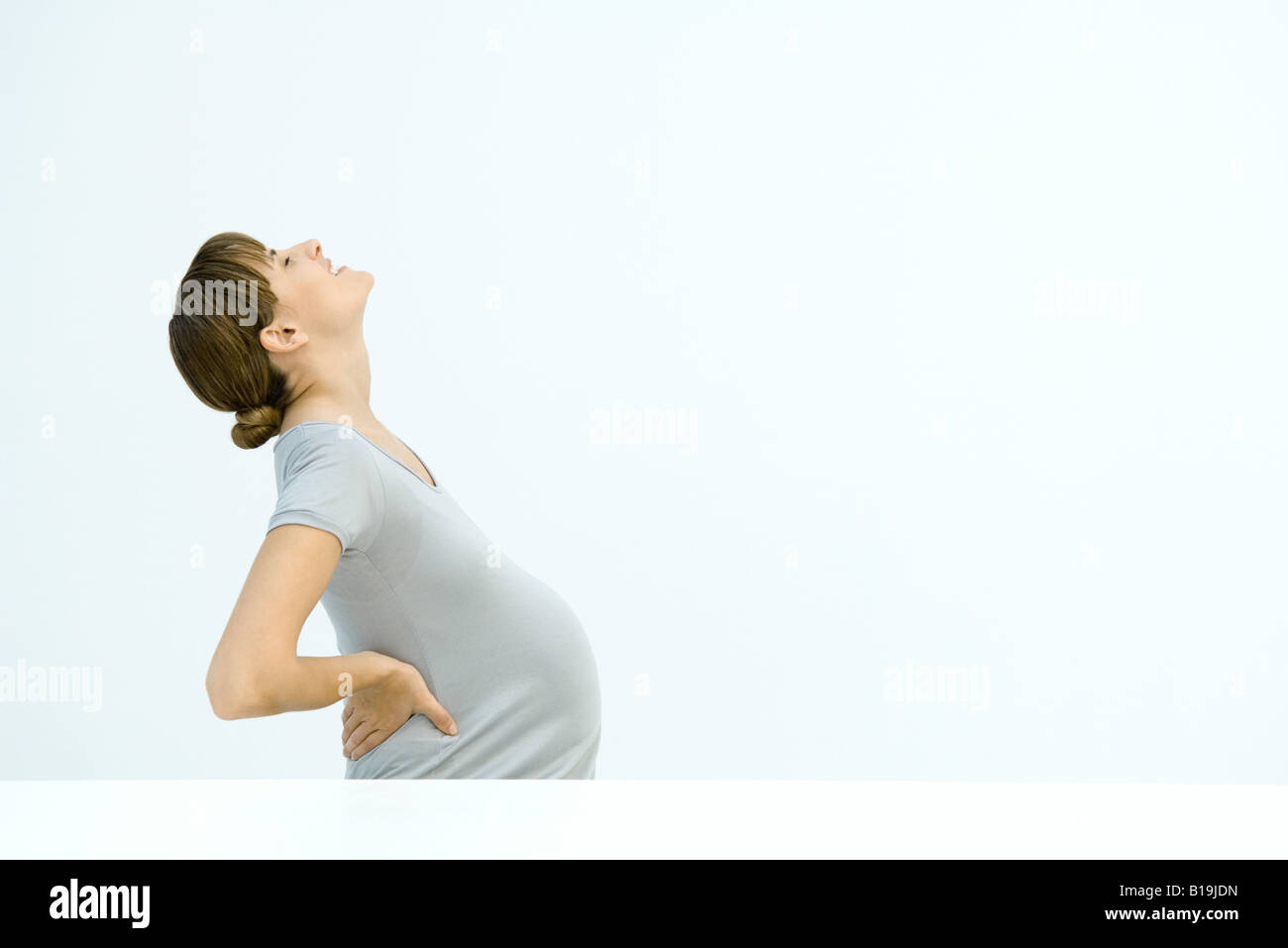 Pregnant woman holding back, leaning back, gritting teeth - Stock Image