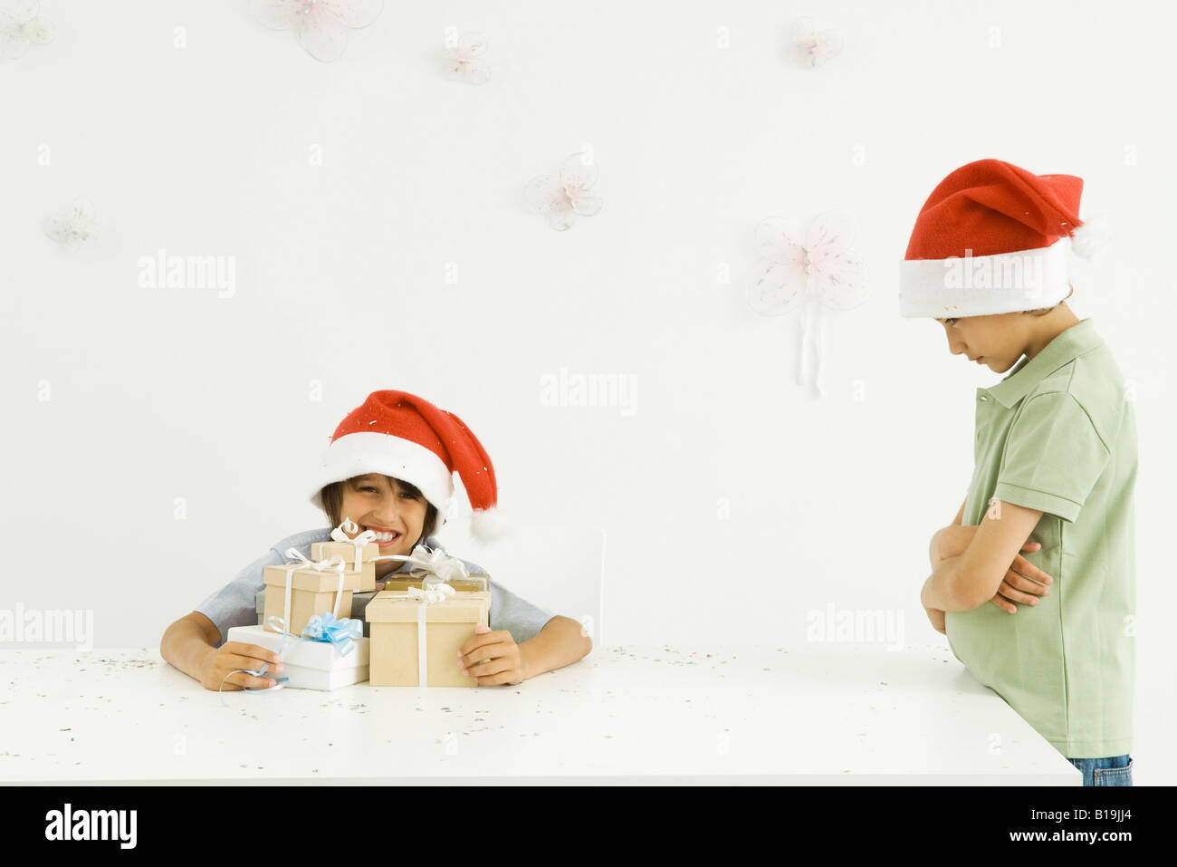 Boy holding stack of Christmas gifts, brother standing nearby Stock ...