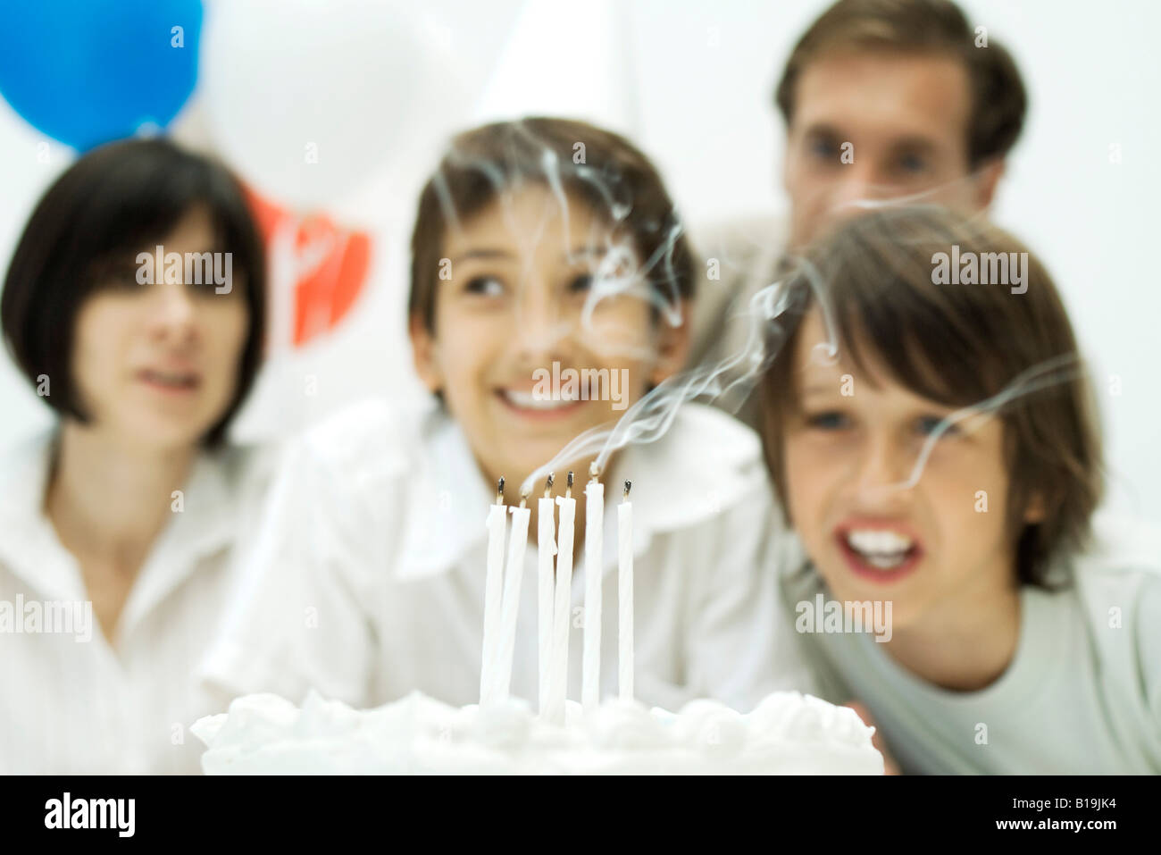 Boys blowing out candles on birthday cake, parents in background - Stock Image