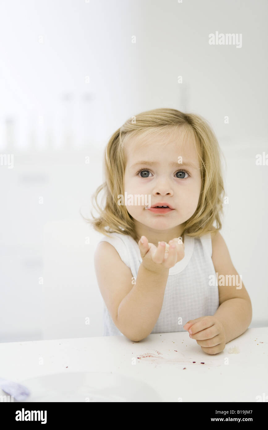 Little girl at table, holding bread in hand, looking up - Stock Image