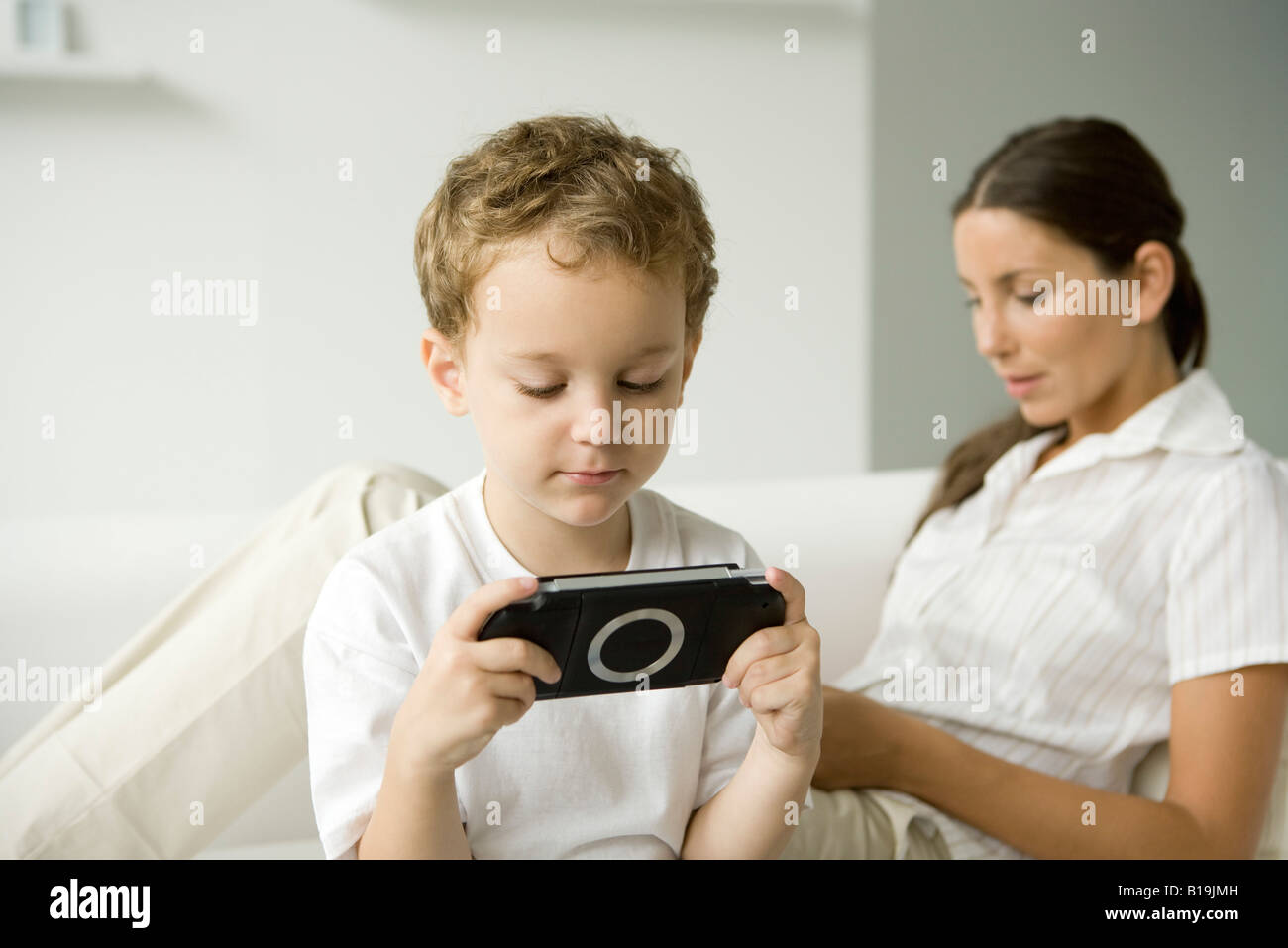 Little boy playing handheld video game, his mother sitting on sofa behind him Stock Photo