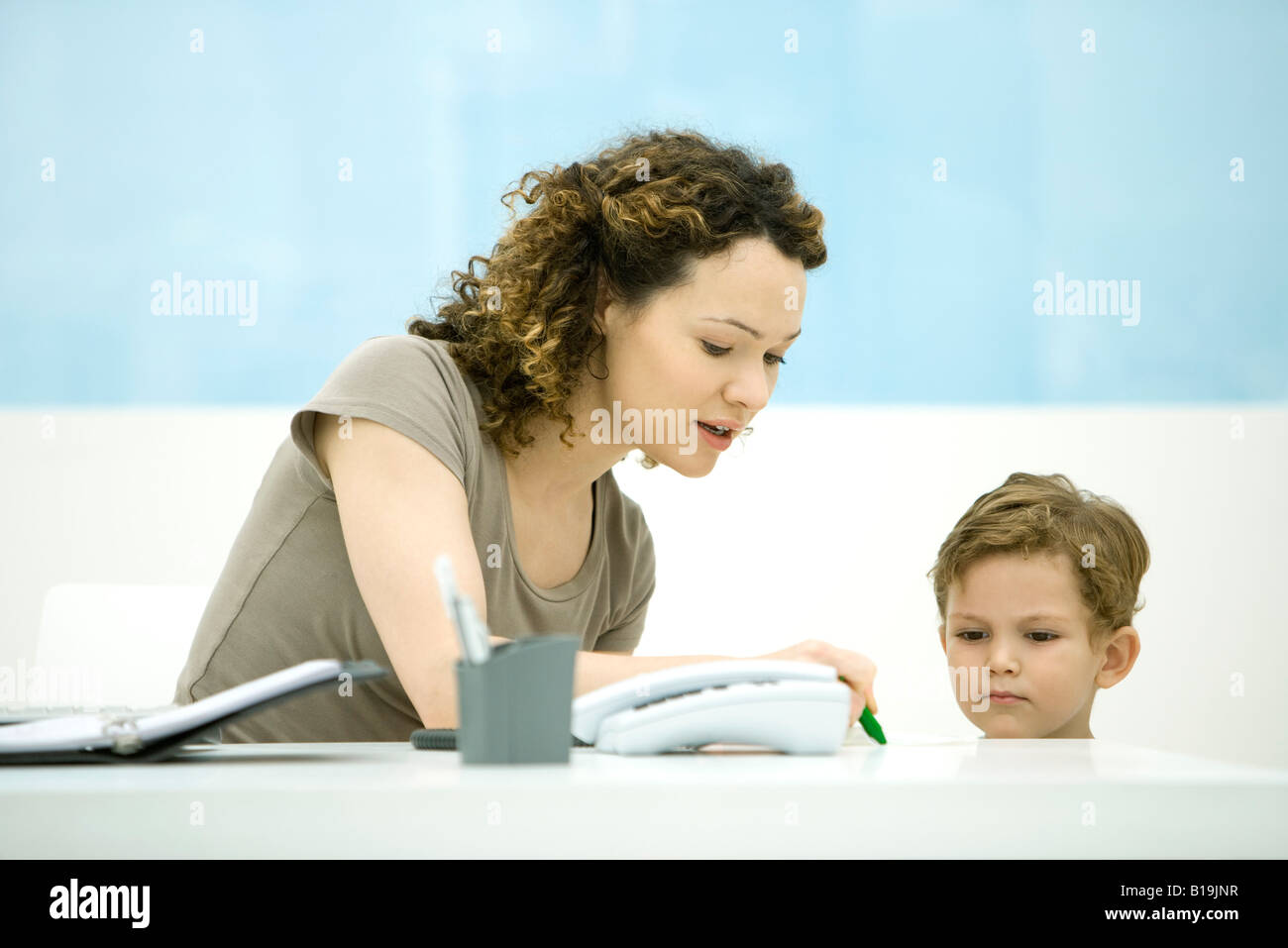 Young mother sitting at desk, interacting with little boy - Stock Image