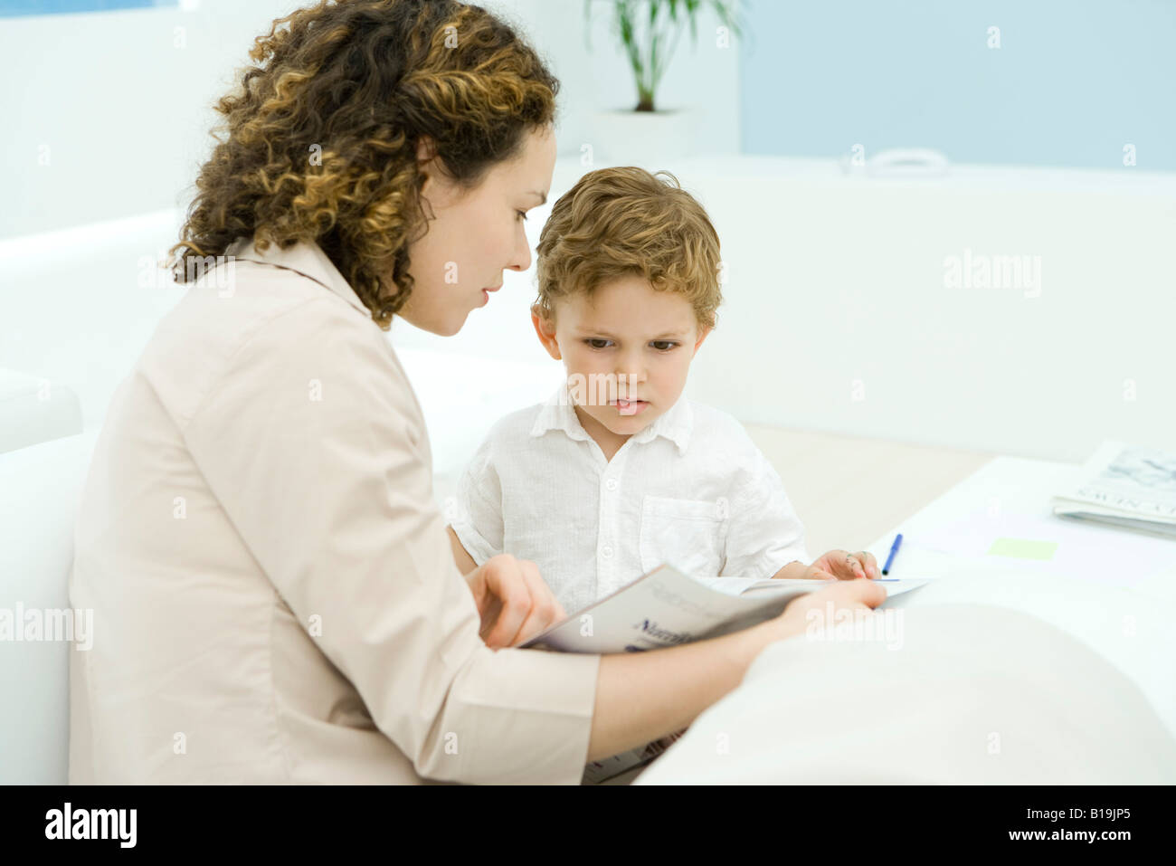 Young mother reading to little boy - Stock Image