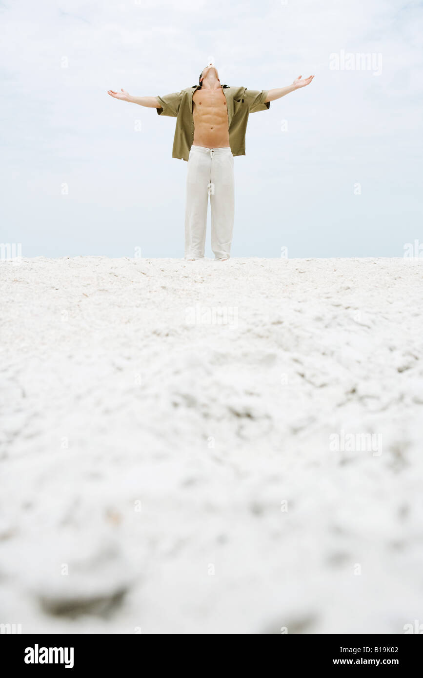 Man standing at the beach with arms out, head back - Stock Image