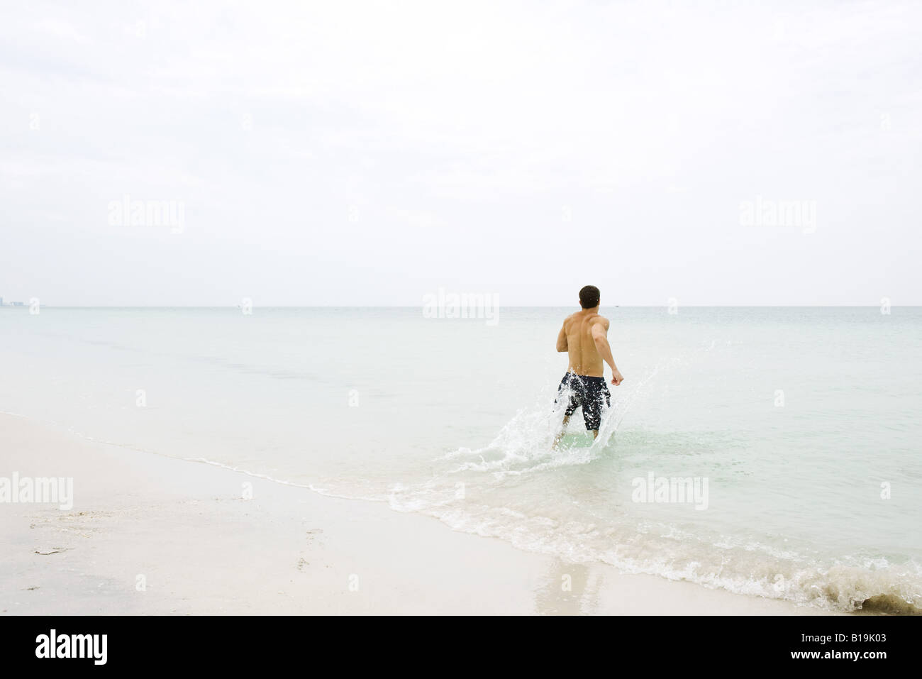Man running in shallow water at the beach, rear view - Stock Image
