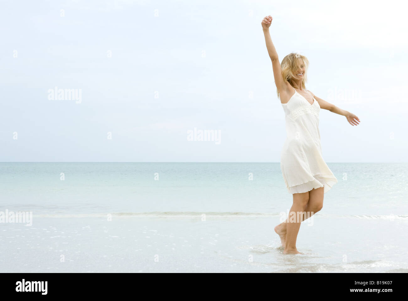 Woman walking at the beach, arms raised, hair tousled by wind - Stock Image