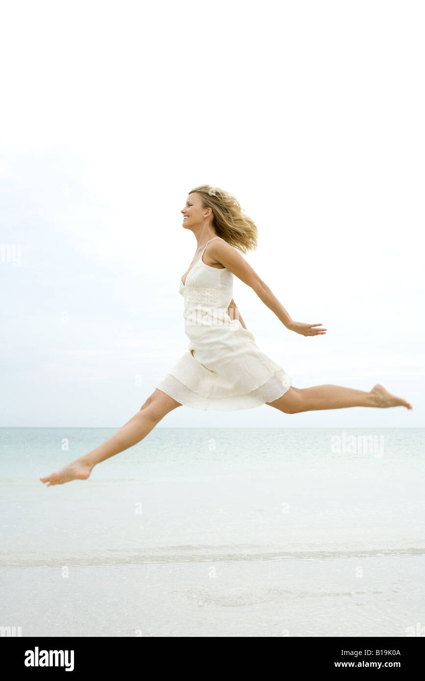 Woman jumping in the air at the beach, side view - Stock Image