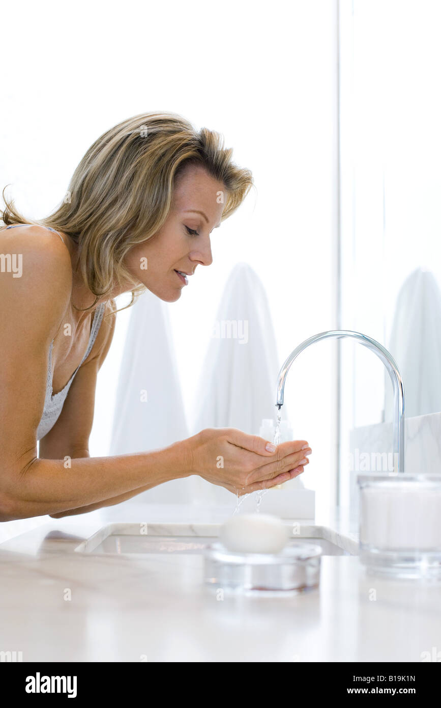 Woman leaning over bathroom sink, holding hands under running water - Stock Image