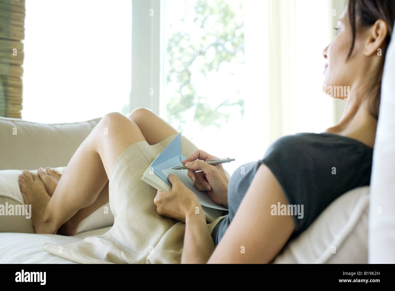 Woman sitting on sofa, holding stationery and pen - Stock Image