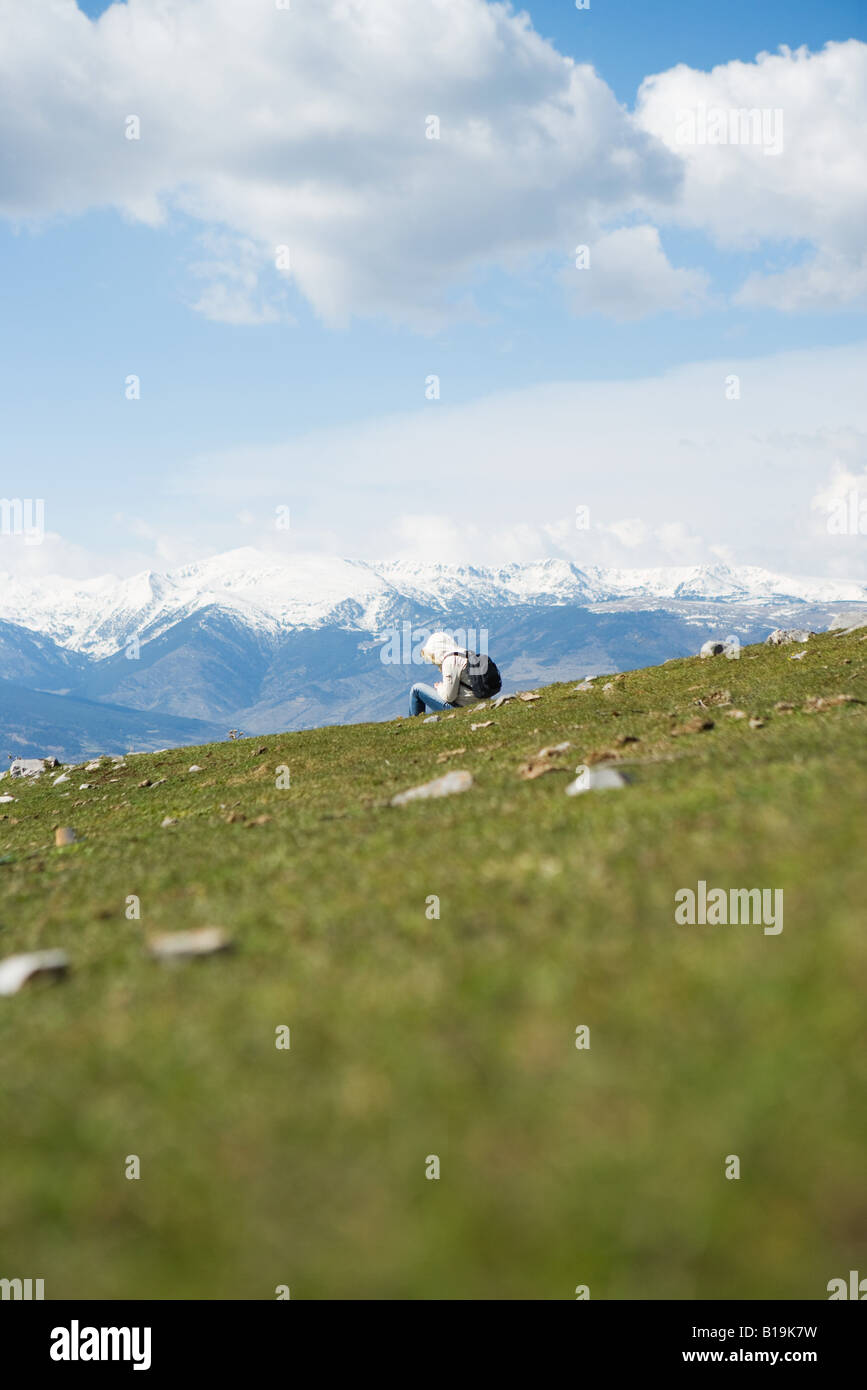 Hiker sitting in mountain landscape - Stock Image