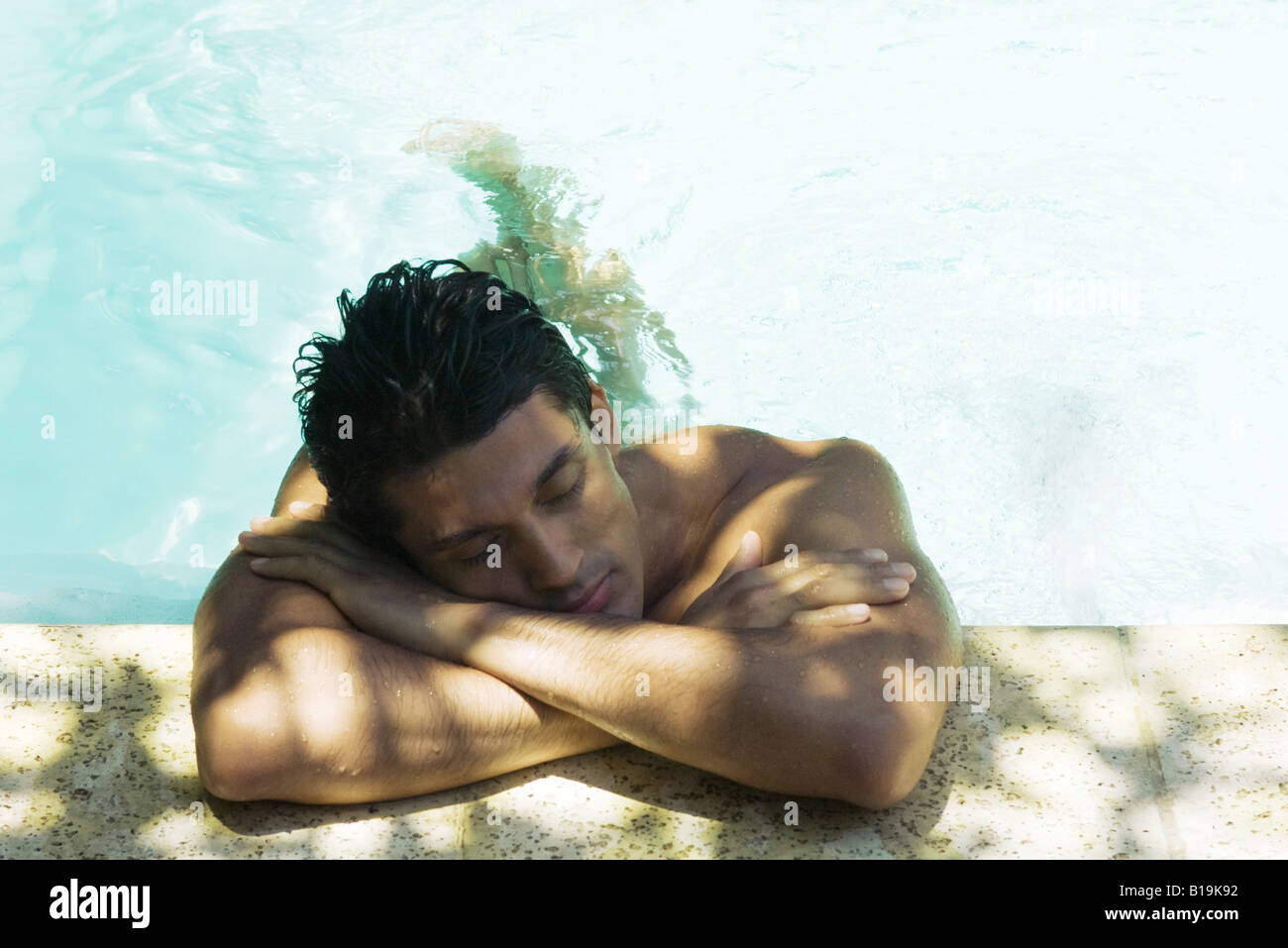 Man resting head on arms on side of swimming pool, eyes closed - Stock Image
