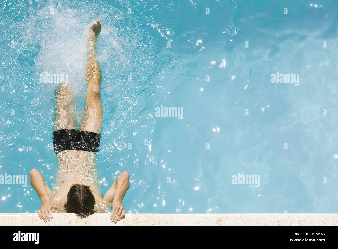 Man holding on to edge of swimming pool, kicking legs, high angle view - Stock Image