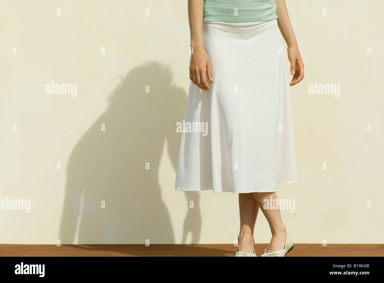 Woman wearing skirt, legs crossed at ankle, cropped view - Stock Image