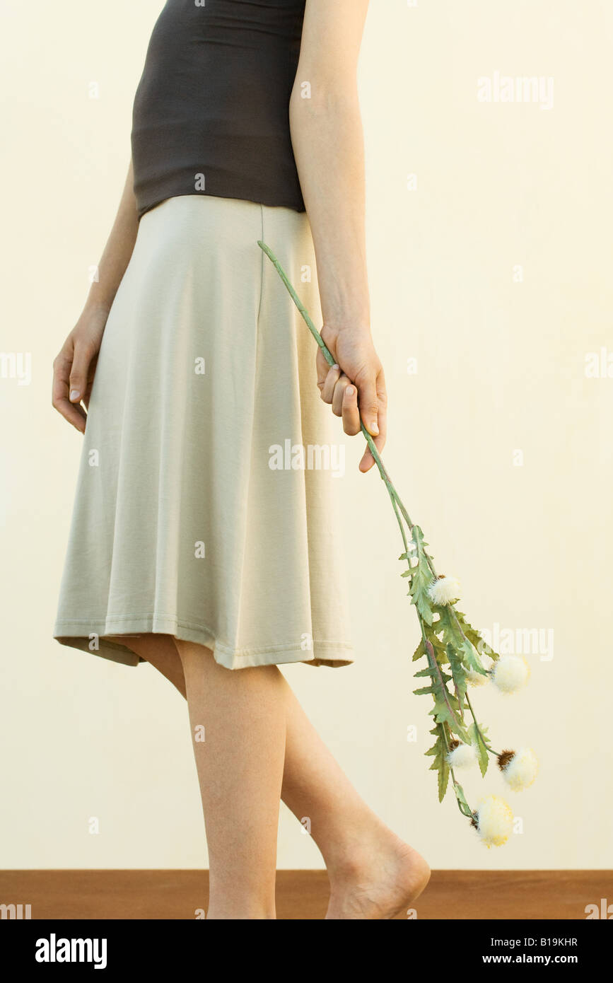 Woman in skirt holding flowers, cropped view - Stock Image