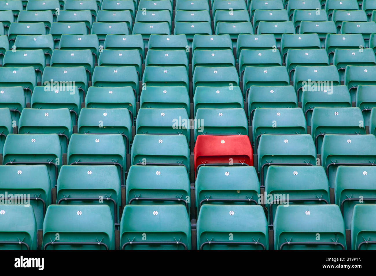 One red seat amongst rows of green seats in a sports stadium - Stock Image