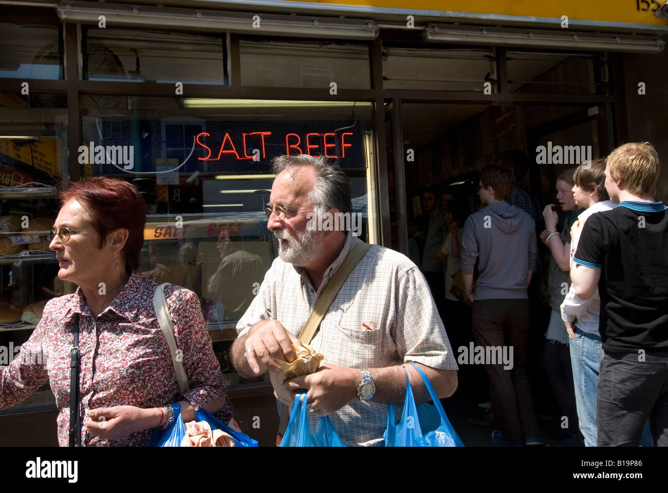 Brick Lane Sunday June 8th 2008 A couple leaving the Salt Beef shop where they have bought rolls - Stock Image