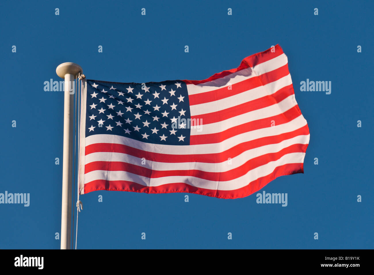American Flag Blowing In The Wind On A Blue Sky Background. - Stock Image