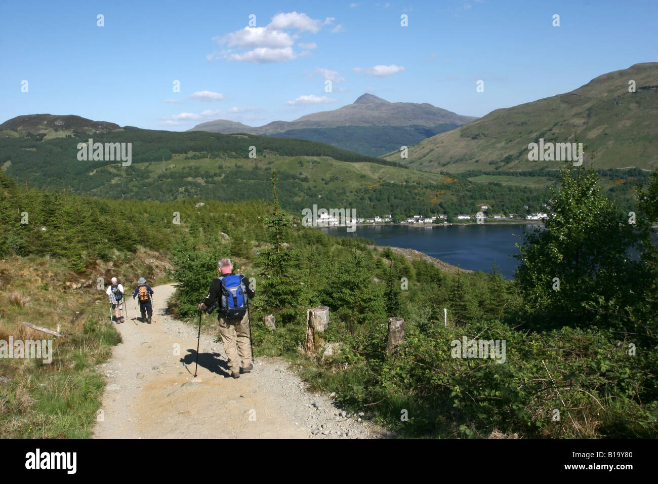 Hikers descending on path from Ben Arthur The Cobbler with Arrocher and Ben Lomond in the background - Stock Image