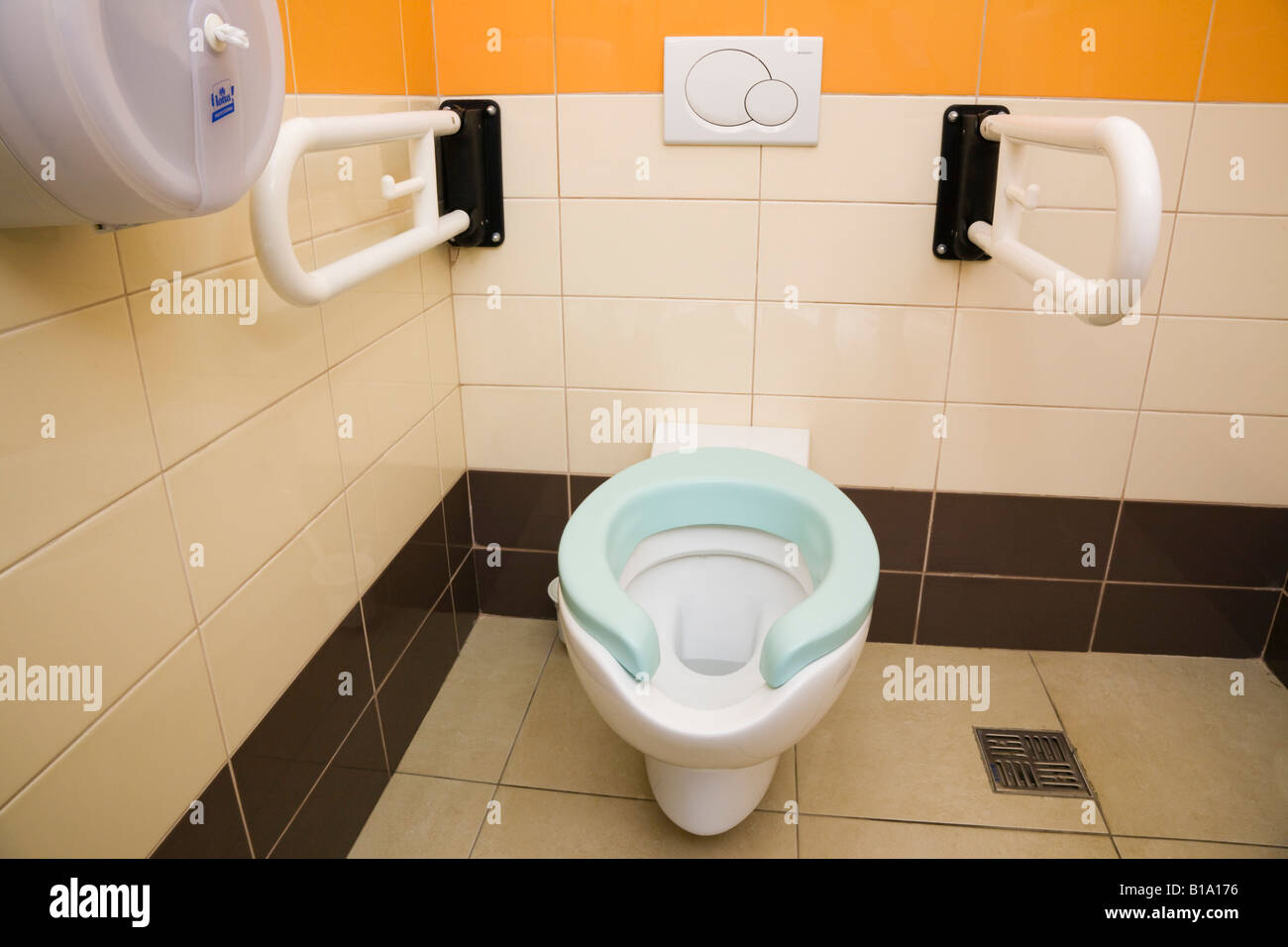 Public Disabled Toilet Inside Clean Tiled Cubicle With Dual Flush Button On Wall And Drop Down Handrail Supports