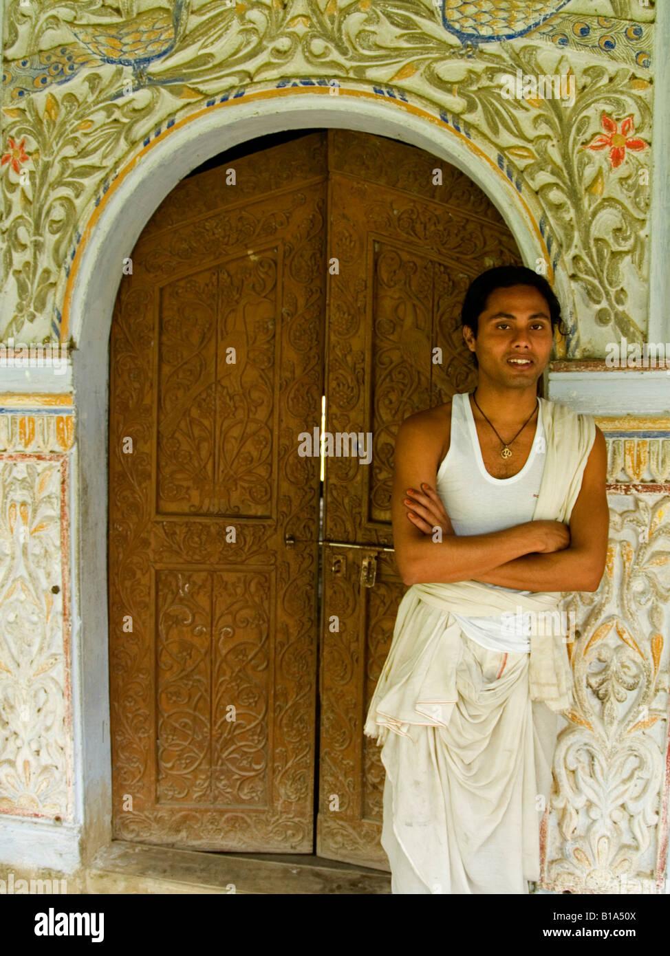 Vishnavaite monk standing in wooden monastery doorway on Majuli Island in India - Stock Image