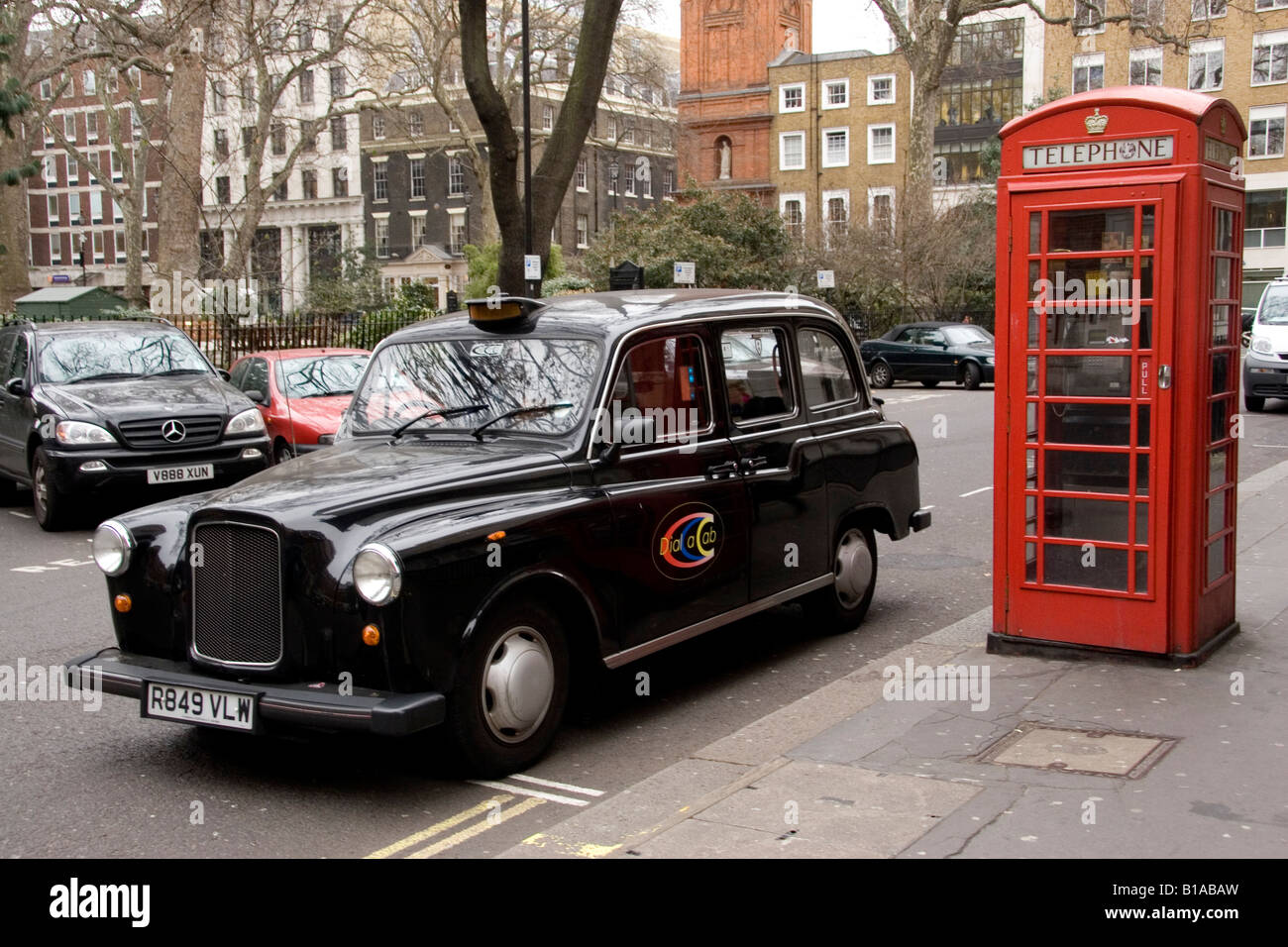 Two of the well known symbols of London. A black Hackney Cab and a red public telephone box. - Stock Image