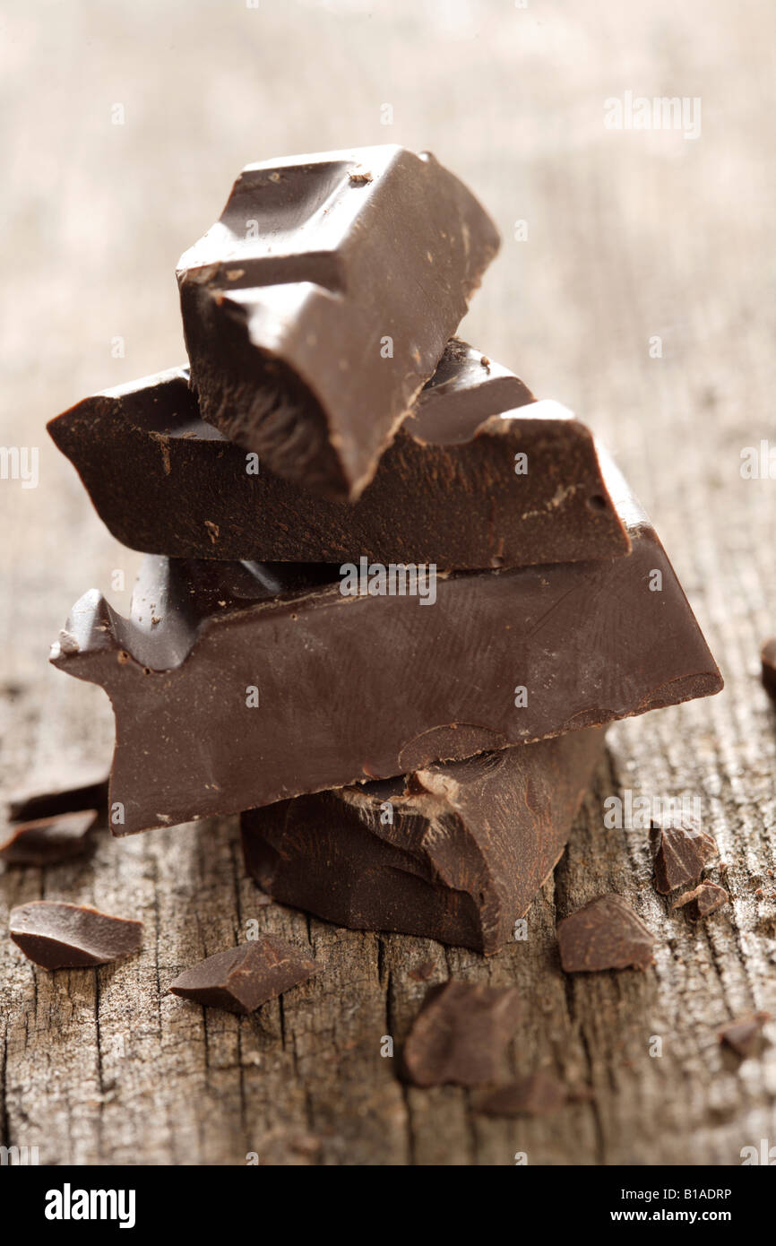 Piled-up chocolate pieces (vertical) - Stock Image