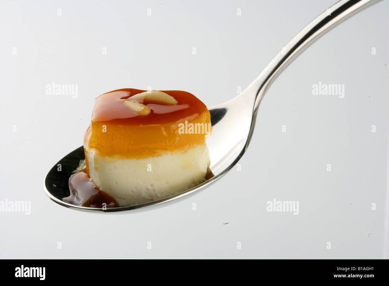 Cheese cream with tocinillo de cielo, caramel syrup and pine nuts on a spoon - Stock Image