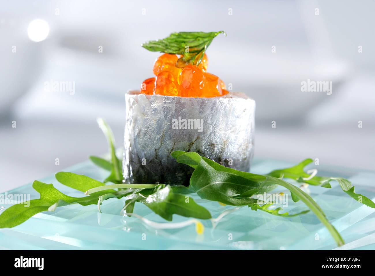 Marinated sardins with salmon eggs - Stock Image