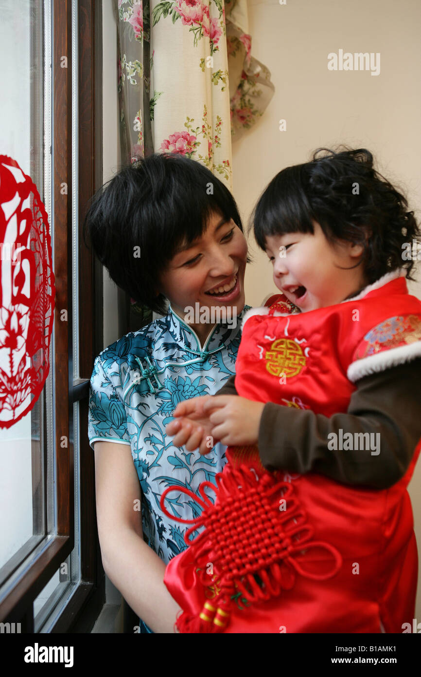 Chinese mother holding her daughter looking at camera smiling Stock Photo