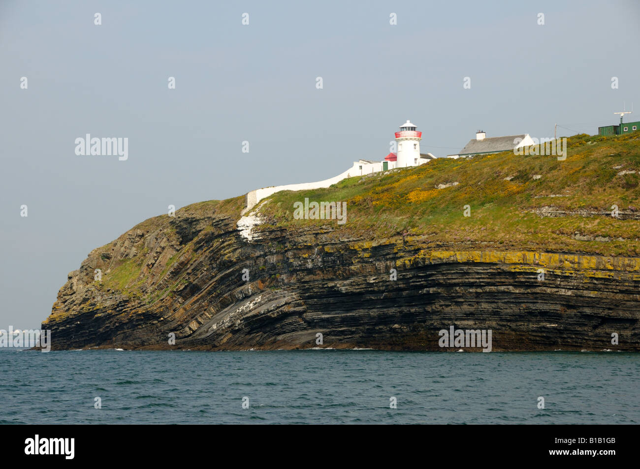 A lighthouse stands on the rock cliff of Irish coast. - Stock Image