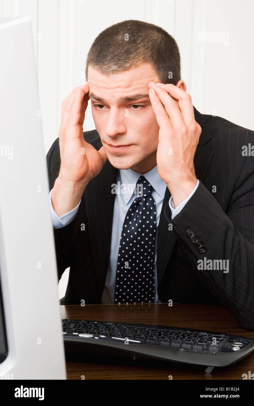 Businessman with hands on forehead looking at pc-screen, close-up, portrait - Stock Image