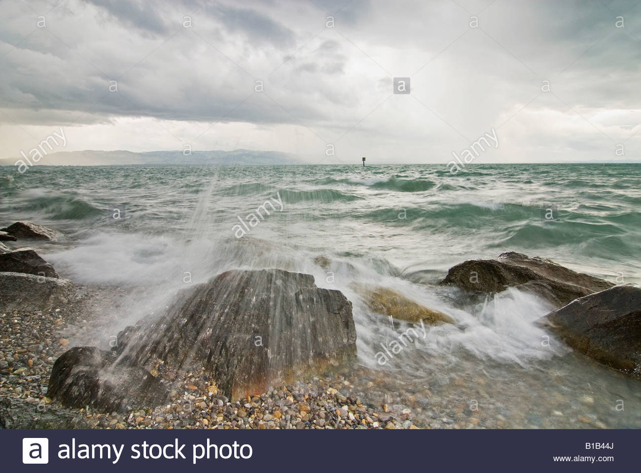 Germany, Bodensee, Nonnenhorn, breaking waves and cloudy sky - Stock Image