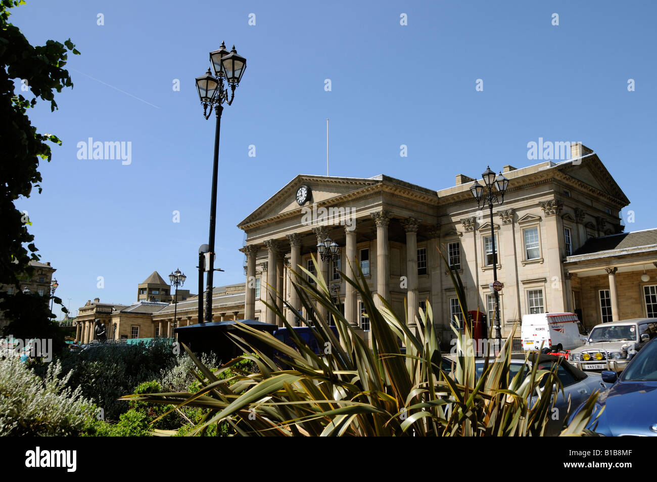 The entrance of the impressive Victorian railway station with ornamental plants in front in Huddersfield - Stock Image