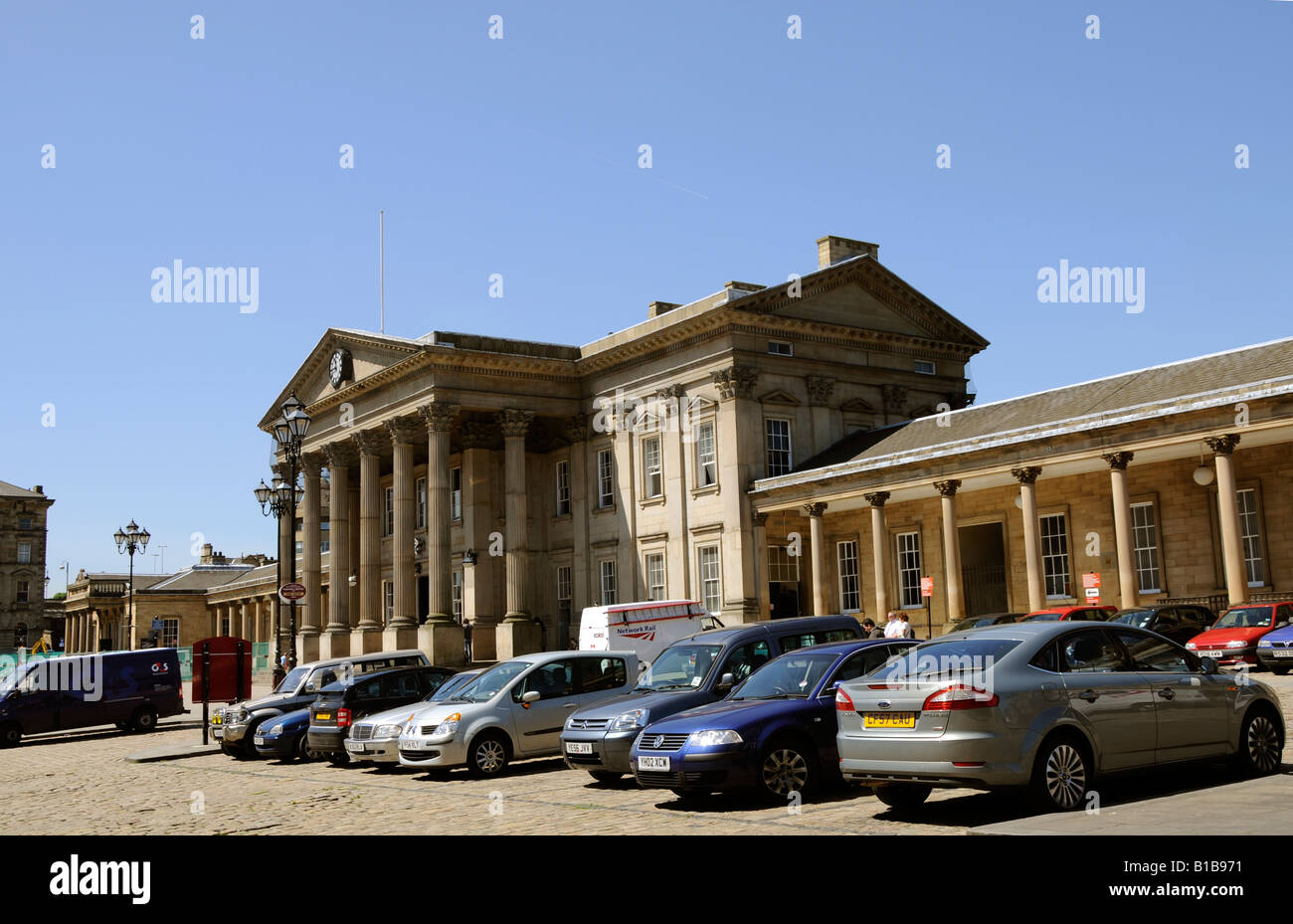 The classical colonnade and portico of the grand entrance of the Victorian railway station in Huddersfield - Stock Image