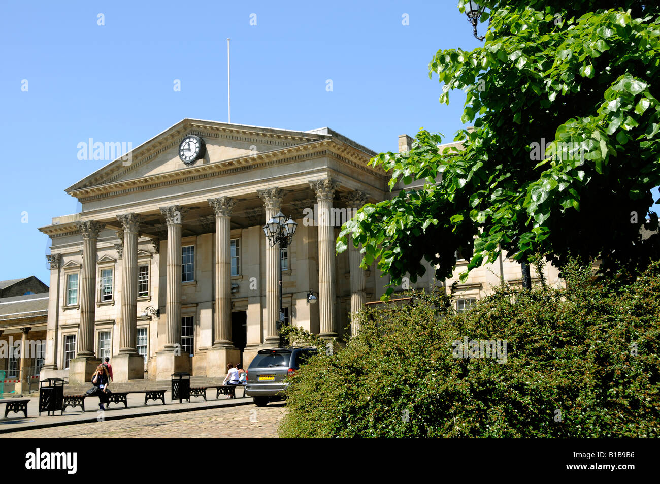 The classical colonnade and portico of the grand entrance of the Victorian railway station seen beyond foliage in - Stock Image
